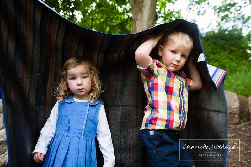 brother and sister under a picnic blanket while in rains heavily - charlotte giddings photographer