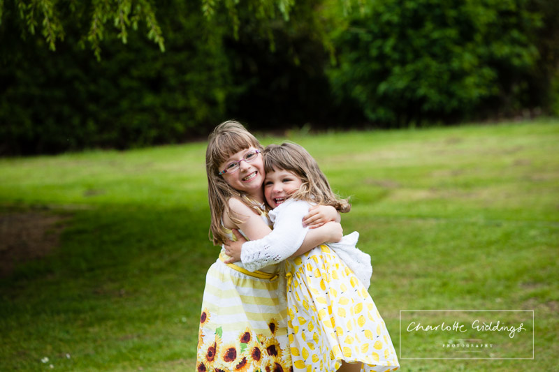 two sisters dressed in yellow giving each other the biggest hug - charlotte giddings photography