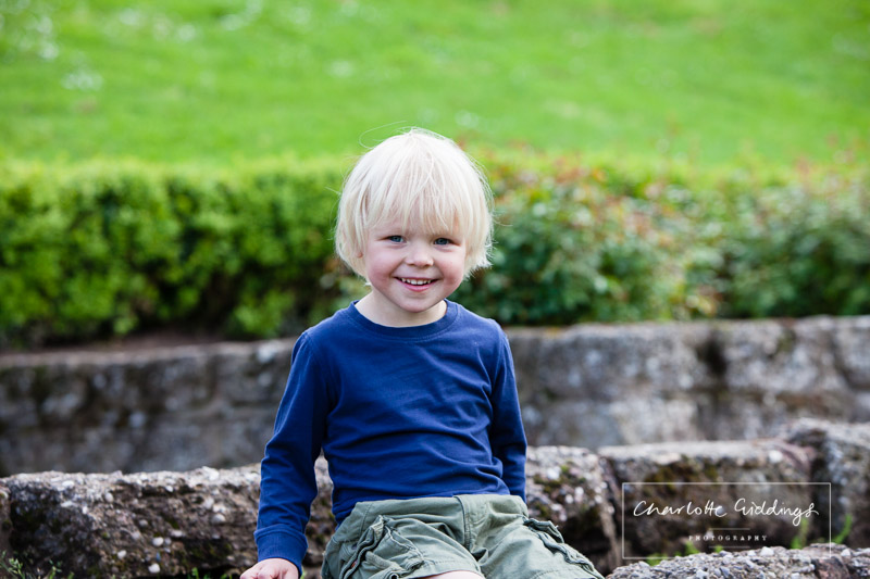 little boy smiling ear to ear sitting down in jubilee park - portrait photographer shropshire