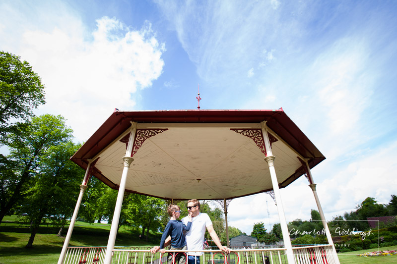father and son looking at one another in the sun, standing in the band stand at jubilee park, shropshire portrait photographer