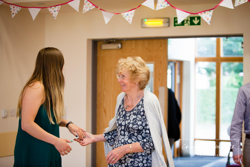 delighted grandma greeting granddaughter as she is surprised at her 80th birthday party