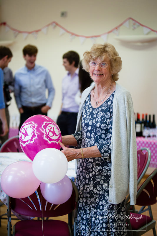 lady who's 80th birthday it is wearing a beaming smile and holding a balloon