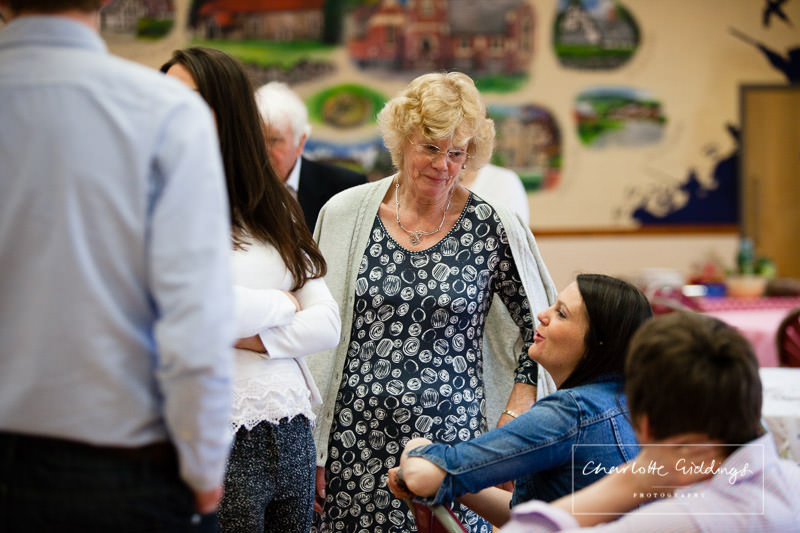 birthday girl listening to her granddaughter telling a tale at her birthday party in llanfechain memorial hall