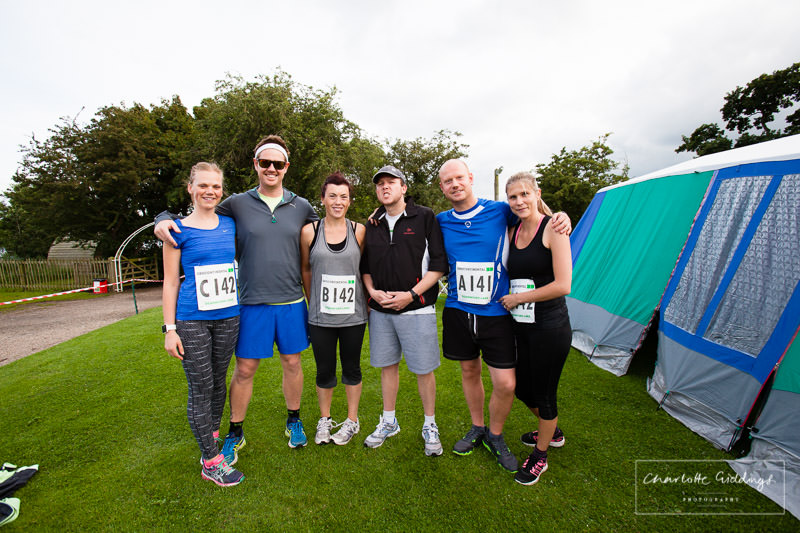 husband and wives teams group photo at dearnford lake before the race