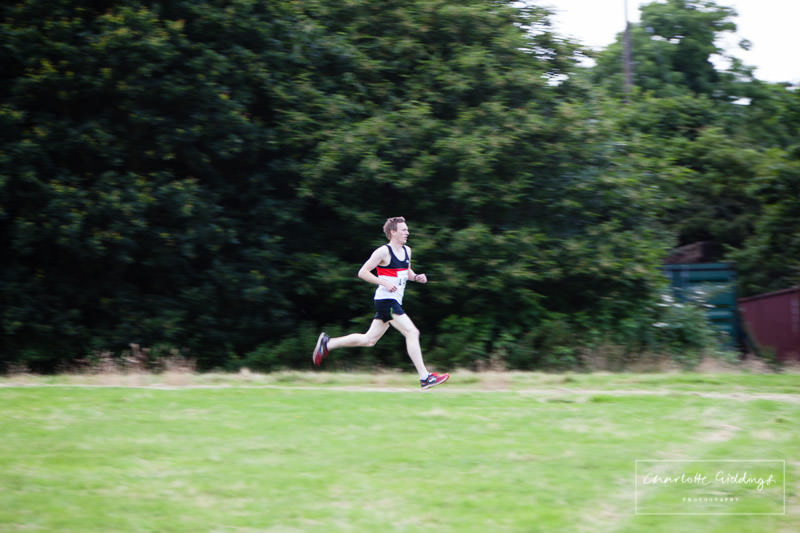 fastest male - shot running past with greenery in the background - in the lead