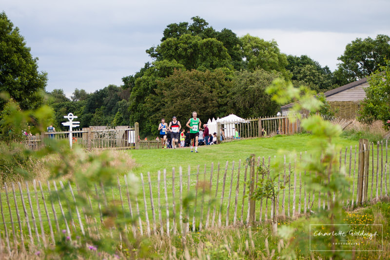runners coming over the brow of the hill with the coffee shop to the right of them at dearnford lake, whitchurch, shropshire
