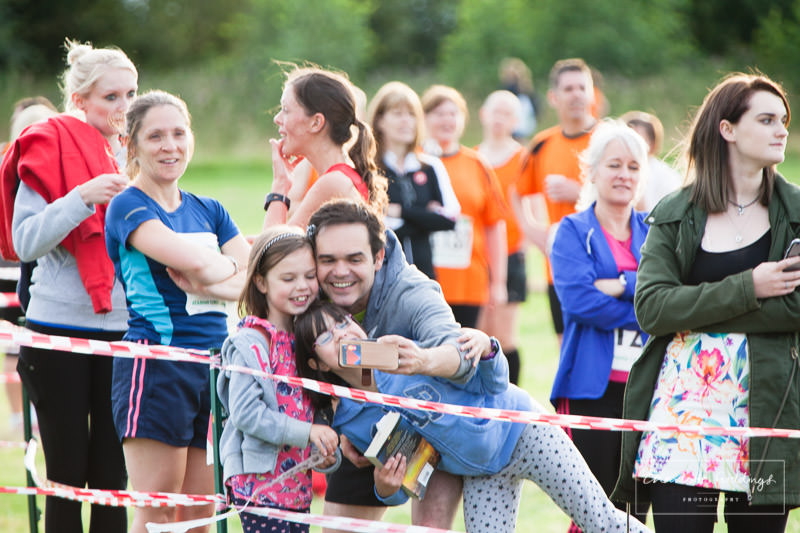 man with two girls taking a selfie on mobile phone at whitchurch running event