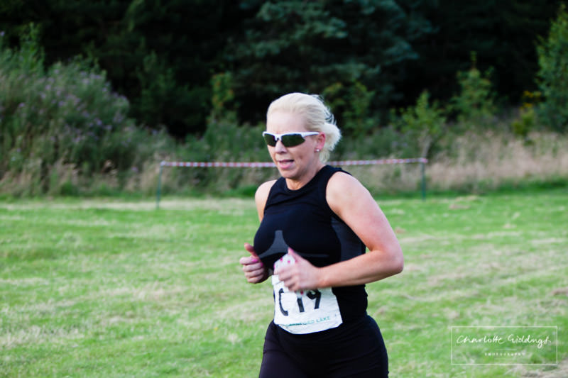 female runner on the last leg for the team approaching the finishing line