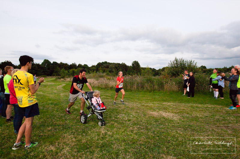 female runner running to the finshing line with partner and baby running with her to the finish line - steve leanord