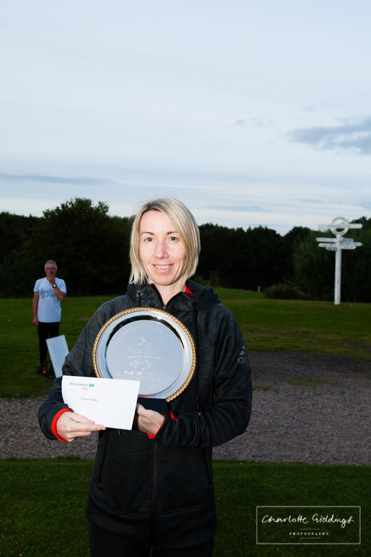 fastest female runner winner with trophy at dearnford lake - with the lake in the background