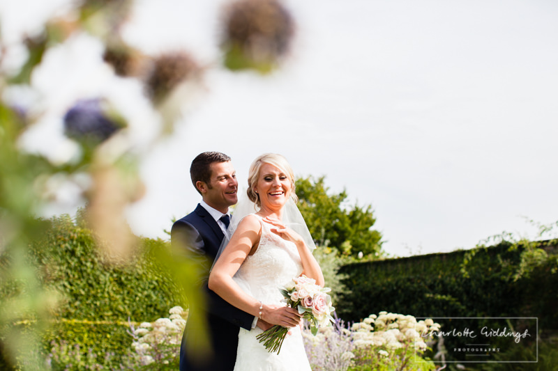 bride and groom giggling in the gardens at combermere