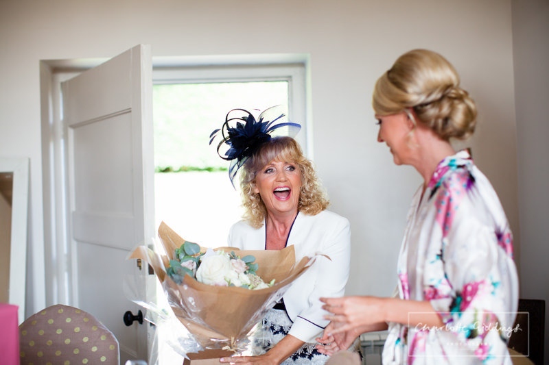 mother of the bride recieving flowers from the bride