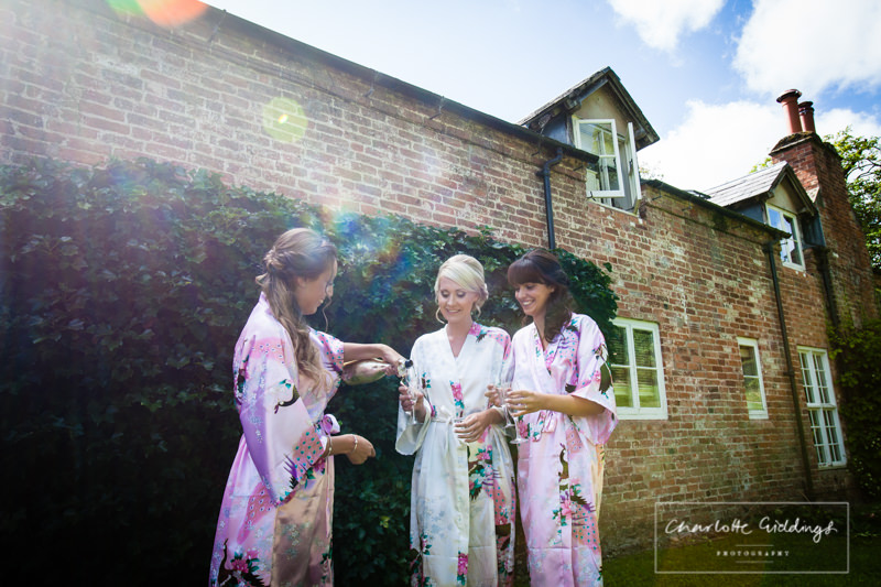 bride and bridesmaids having a champagne toast outside combermere cottages