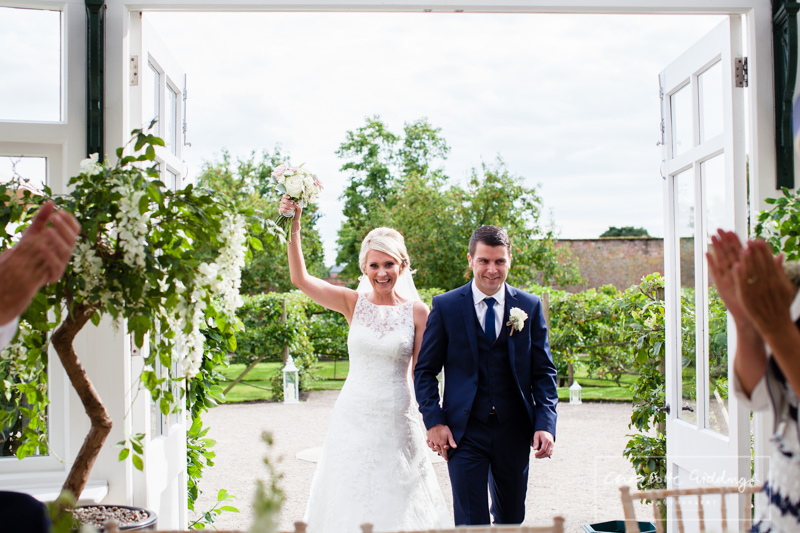 bride and groom entering the wedding breakfast glasshouse