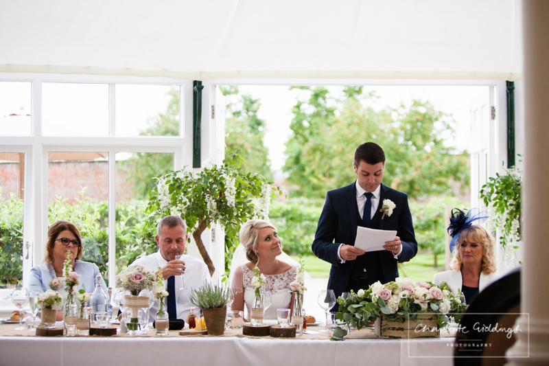 groom reading his speech in glasshouse