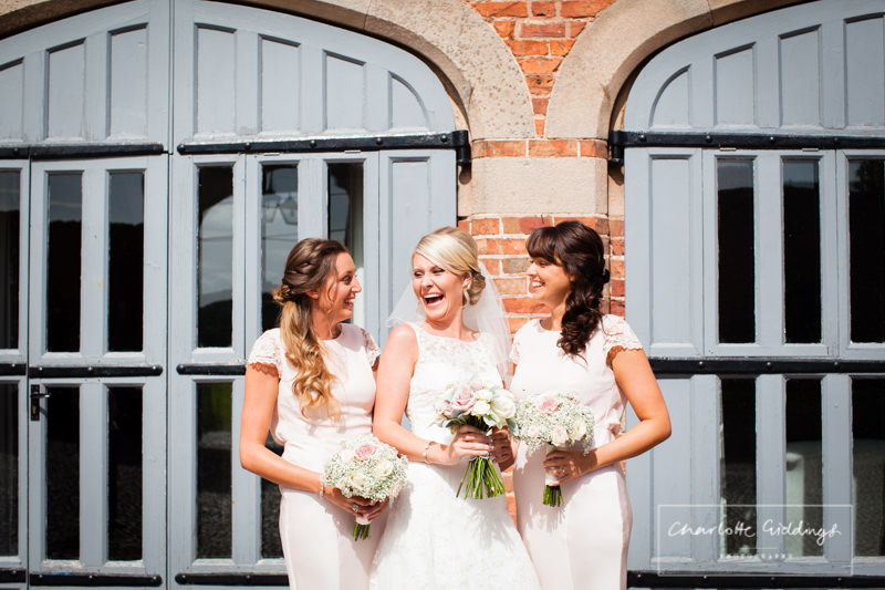 bride and bridesmaids laughing at combermere abbey cottages