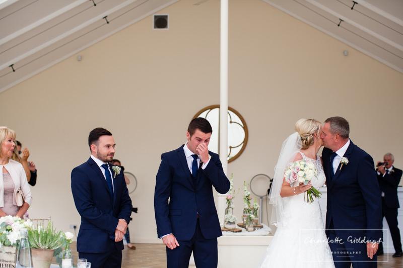 emotional groom bride kissing dad