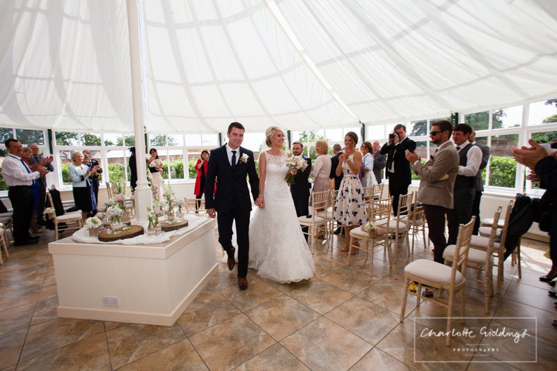 bride and groom walking down the aisle at combermere abbey