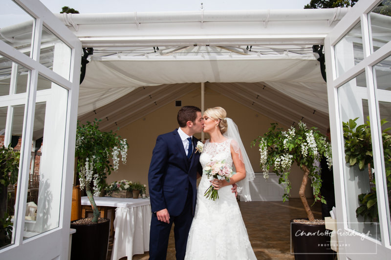 bride and groom kiss outside the glasshouse
