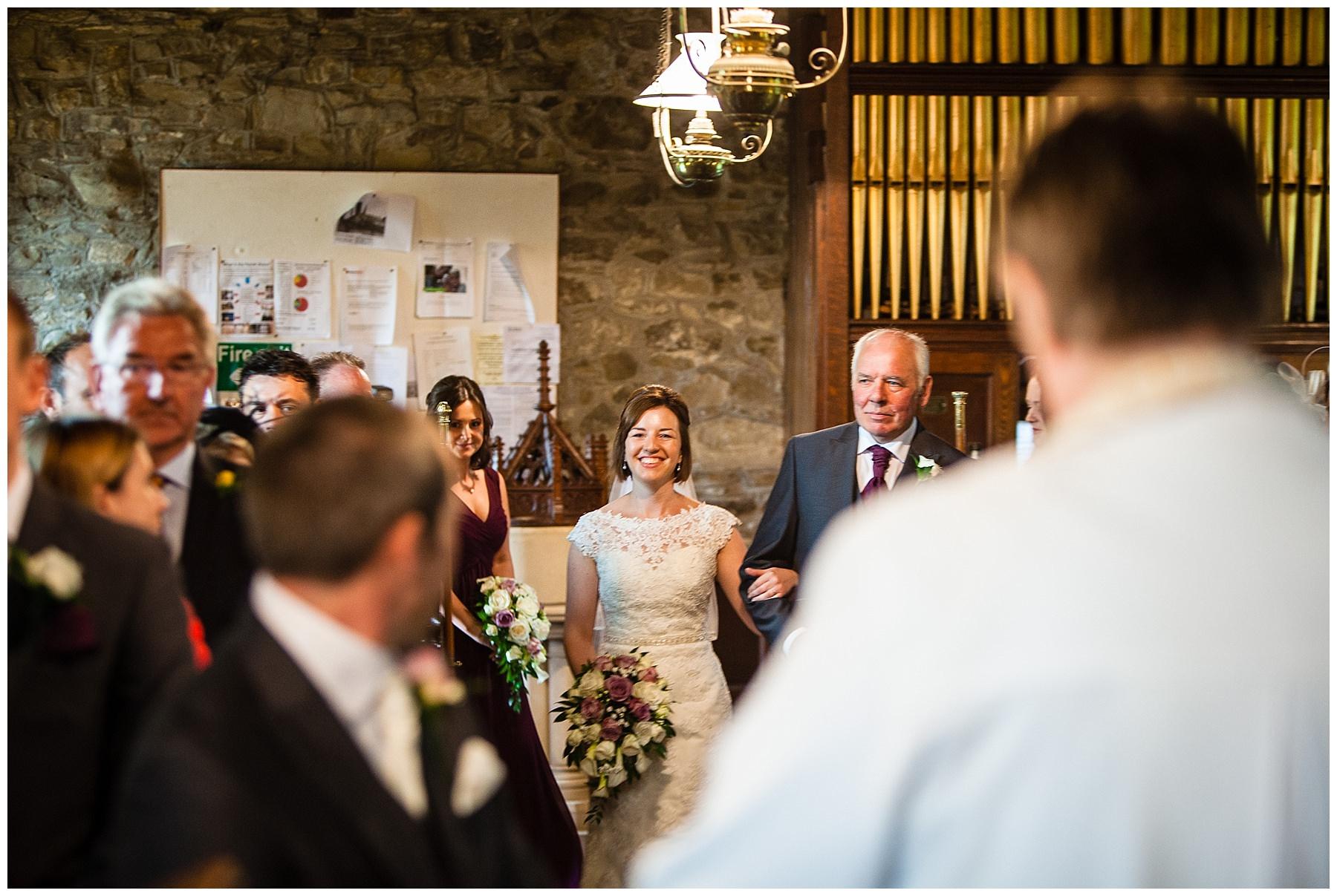 beautiful bride walking down the aisle at St.Llwchaiarn's Church, Llanmerewig
