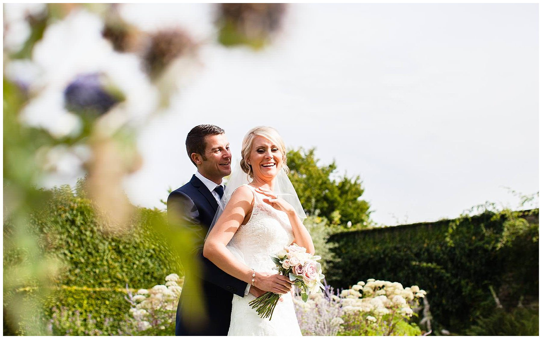 bride groom laughing in the gardens at combermere abbey, whitchurch shropshire