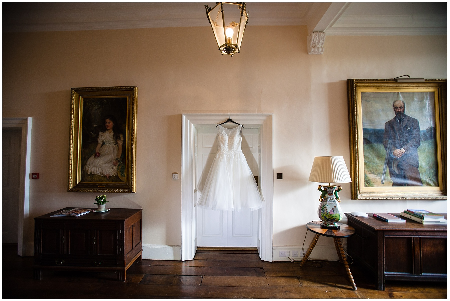 brides wedding dress hanging outside the bridal suite surround by the interior decor of paintings and lamps at iscoyd park