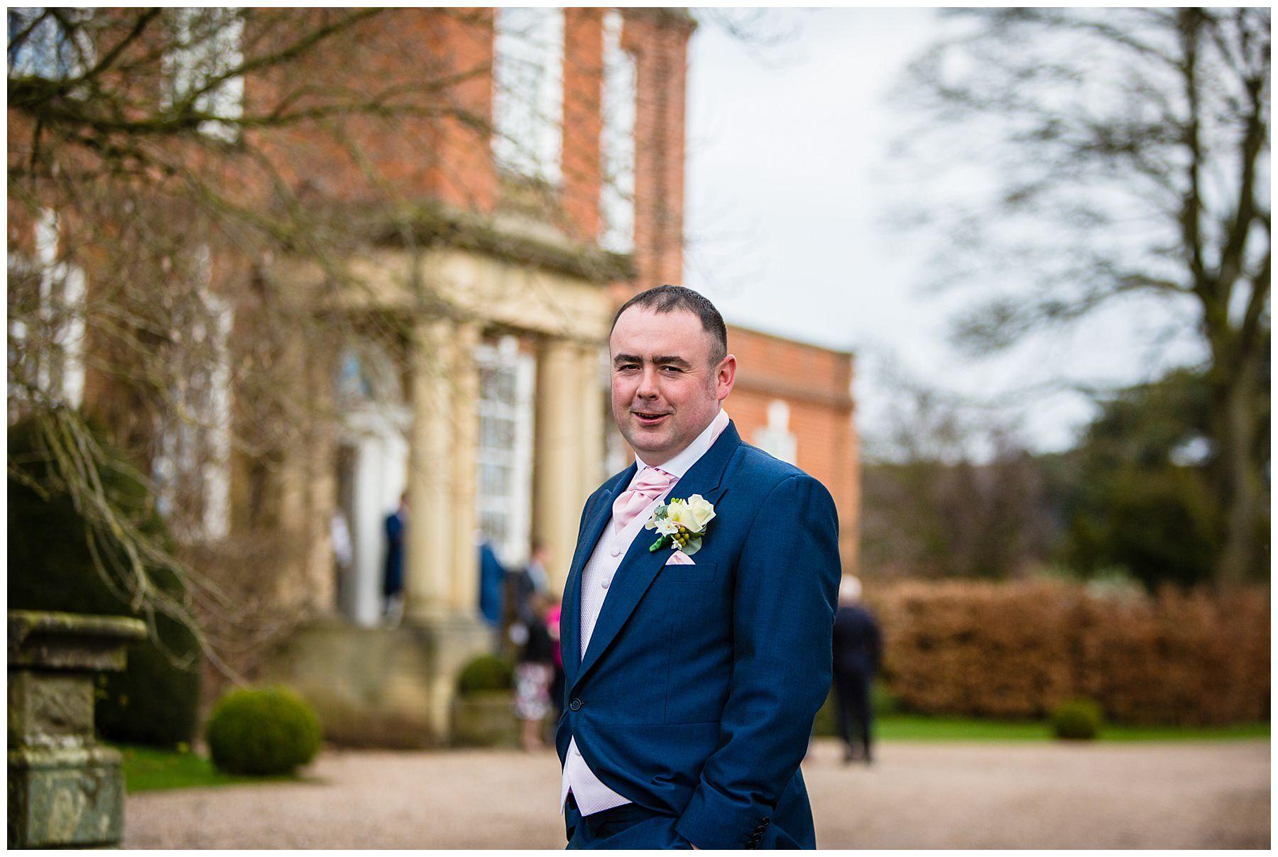 groom portrait in navy suit infront of isooyd park building - iscoyd wedding photographer