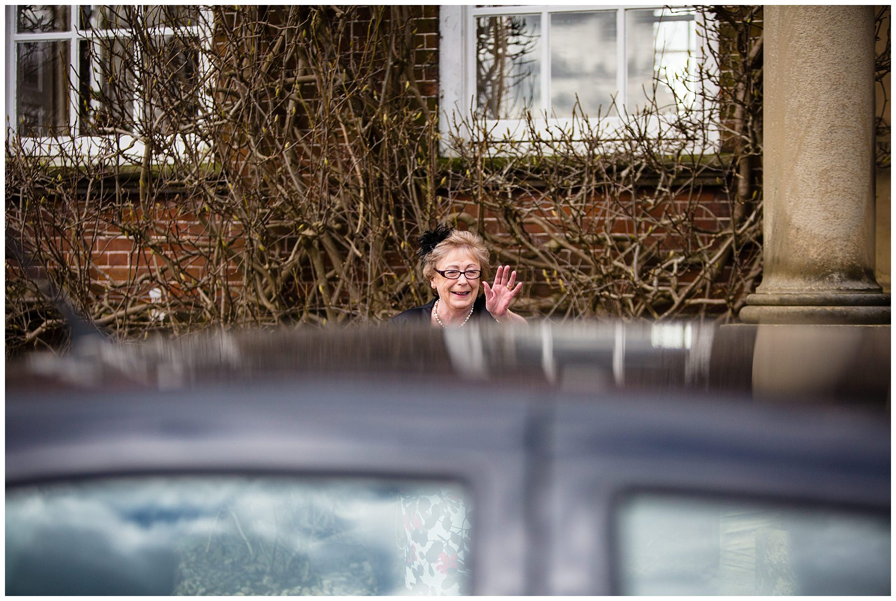 mother of the groom waving to guests as they arrive at iscoyd park wedding