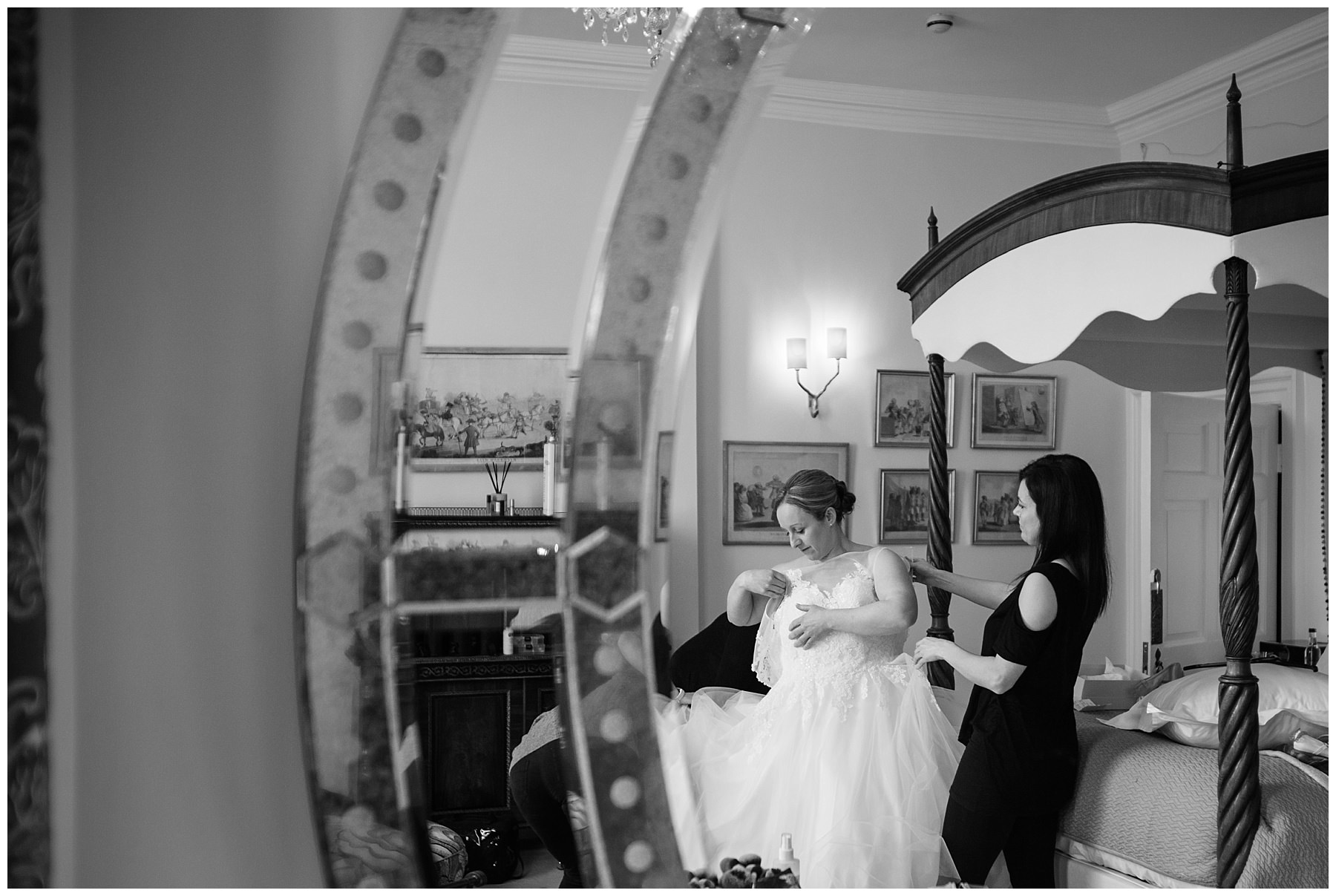 black and white photo of the bride getting into her dress, reflection in the grand mirror in the bridal suite