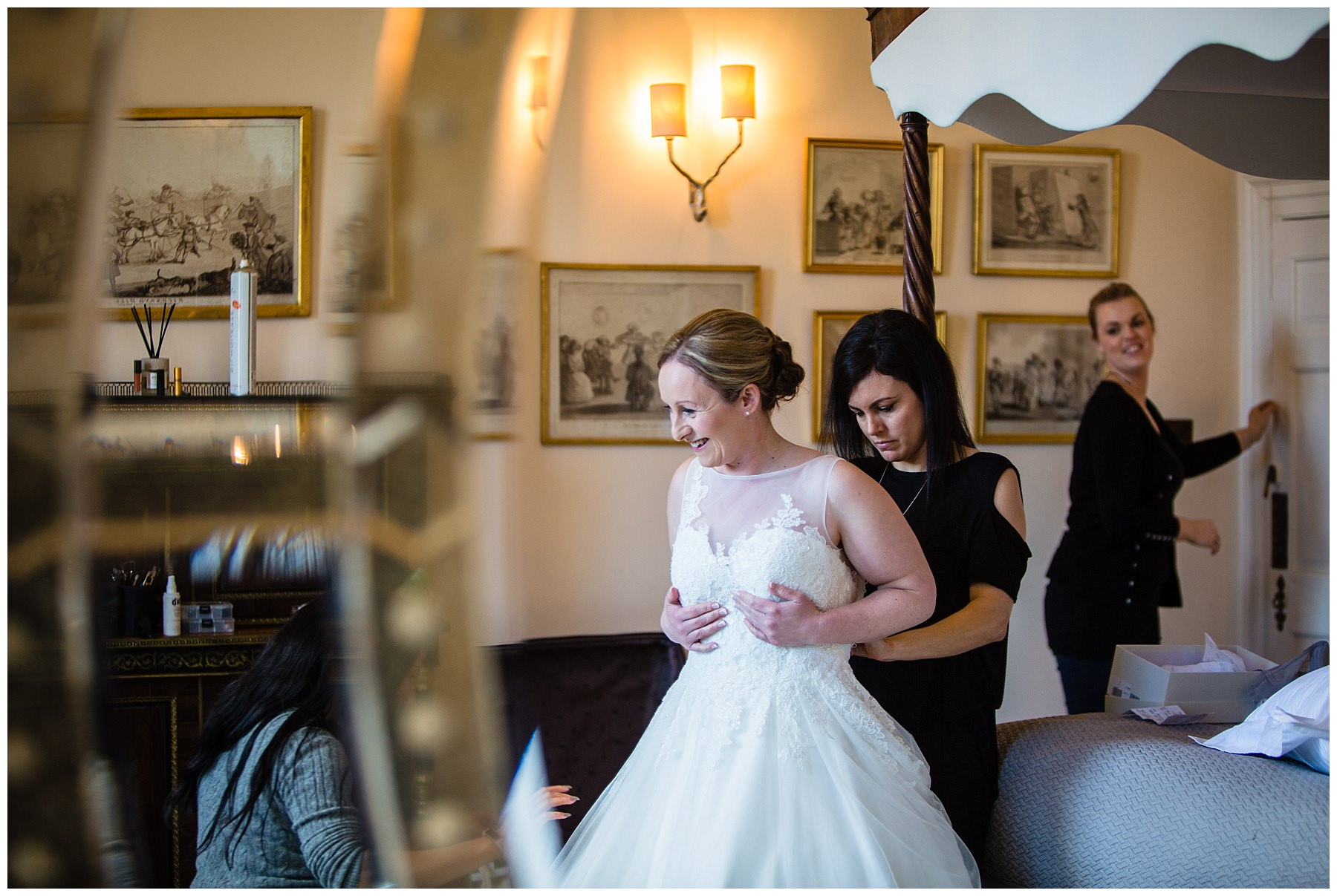 reflection of the bride getting intp her dress in beautiful natural light at iscoyd park wedding