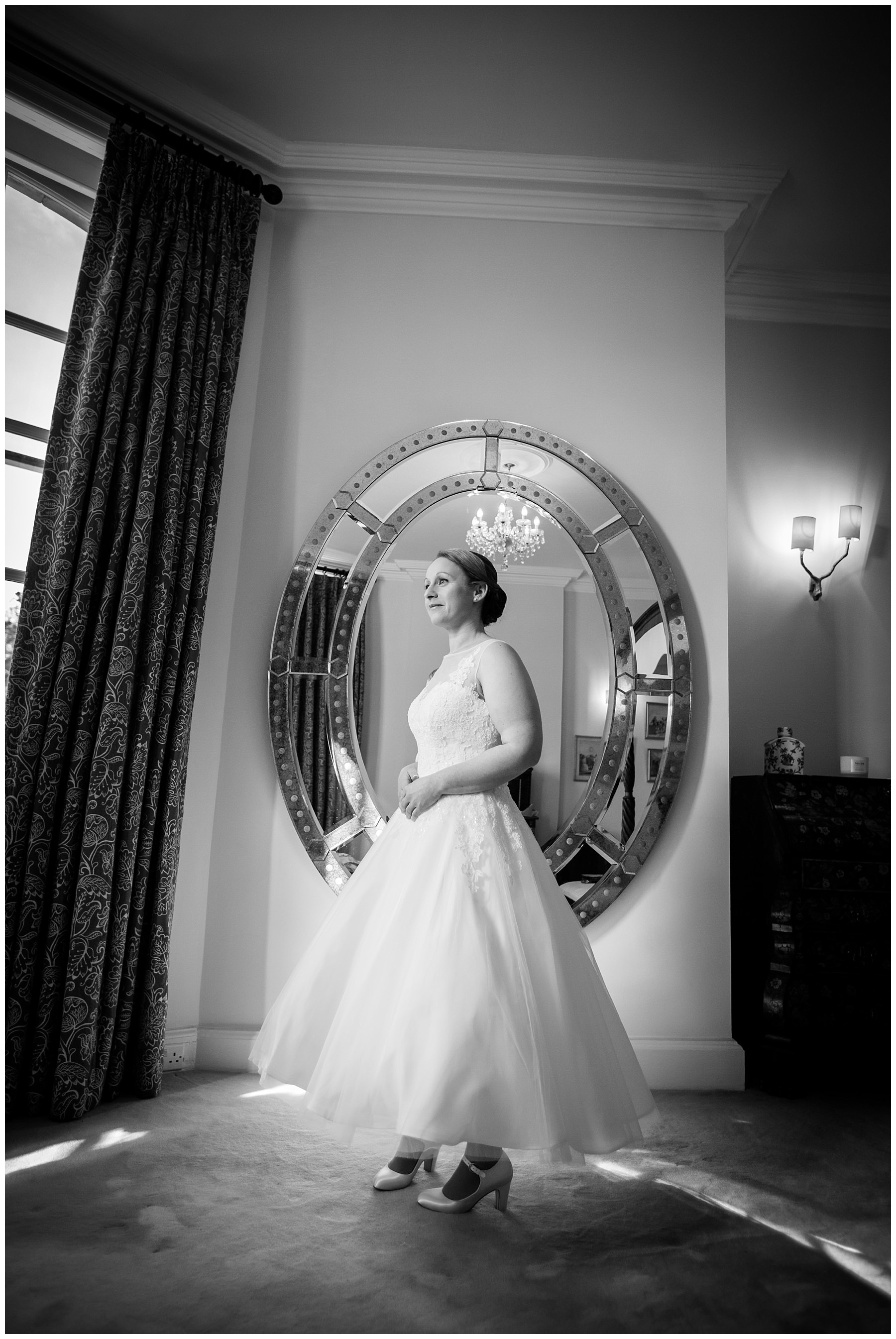 black and white full length photo of the bride fully dressed infront of the grand mirror in iscoyd parks bridal suite