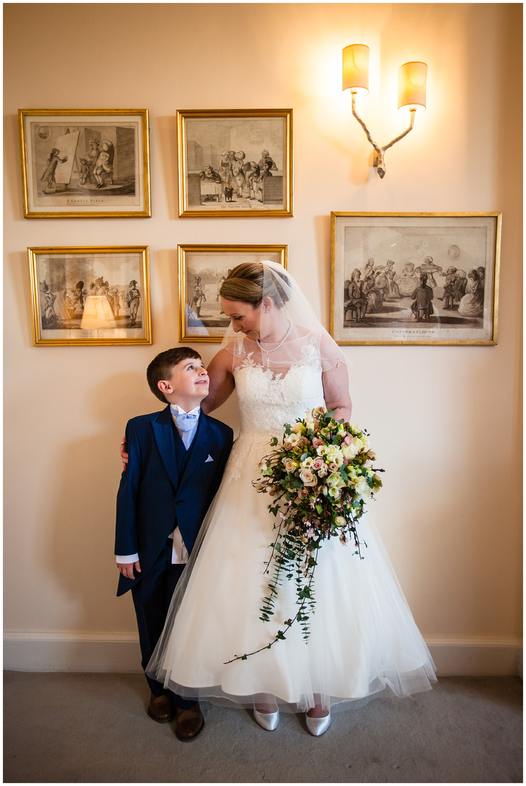page boy looking up his mum ready for her iscoyd park wedding surrounded by beautiful decor