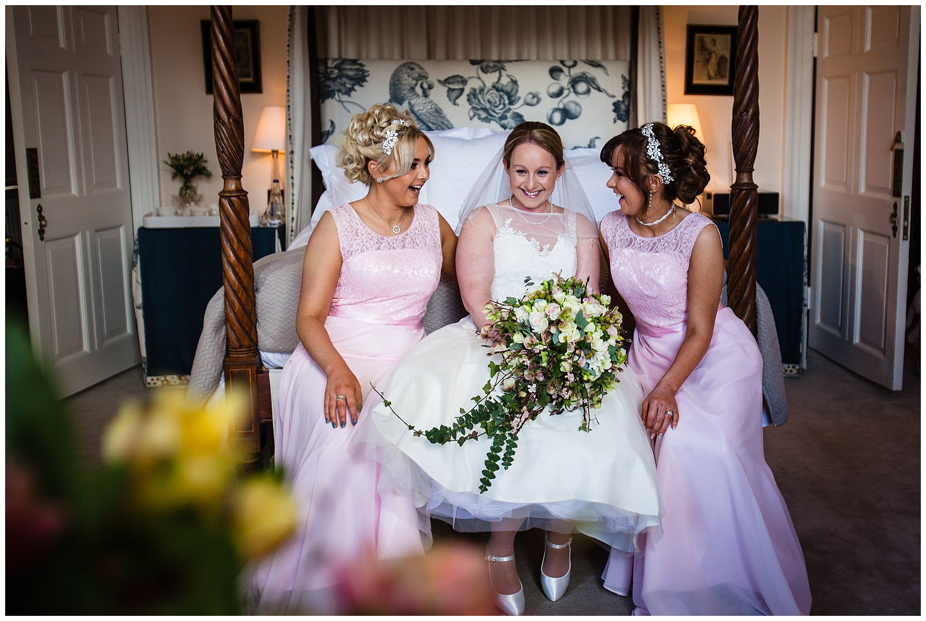 candid photo of the bride giggling with two bridemaids at the end of the bed in the bridal suite