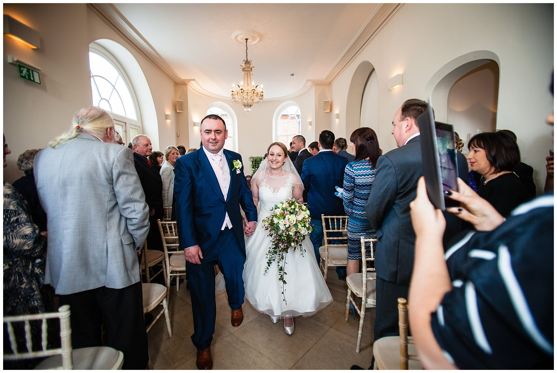 bride and groom walking down the aisle at iscoyd park wedding