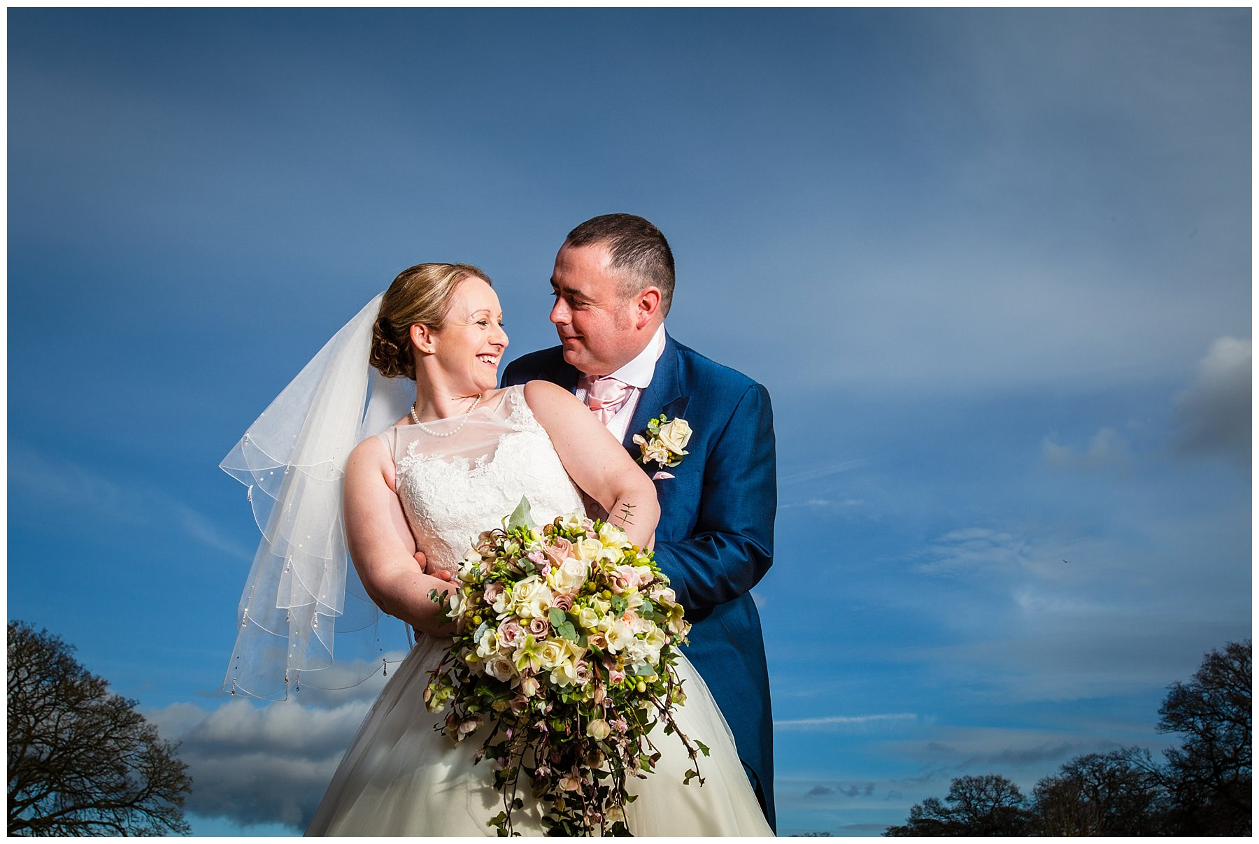 bride and groom smiling at each other lovingly outside win the winter blue sky at their iscoyd park wedding