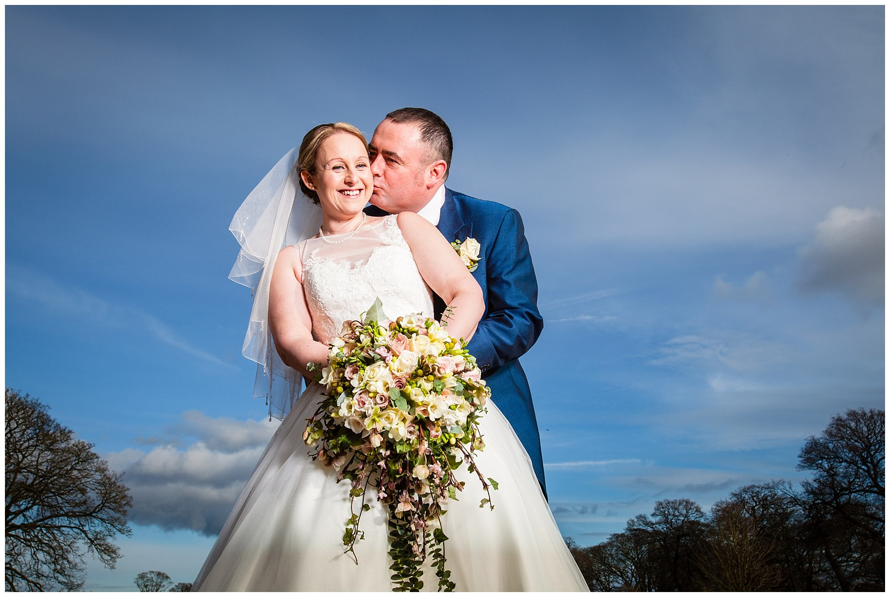 bride looking at the camera very very happy as the groom kisses her cheek shropshire wedding