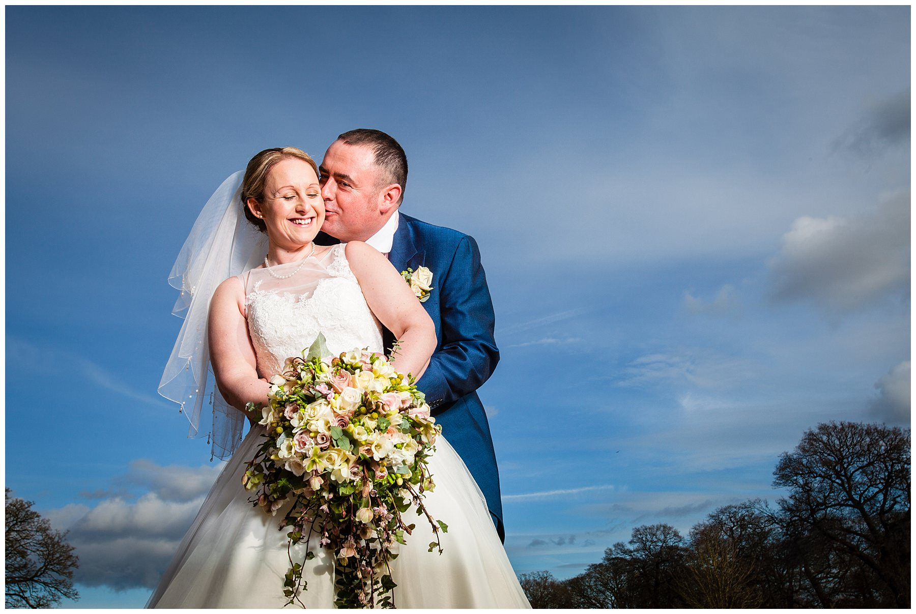 A very happy bride and groom with beautiful blue sky at Iscoyd Park Wedding- Shropshire Wedding Photographer