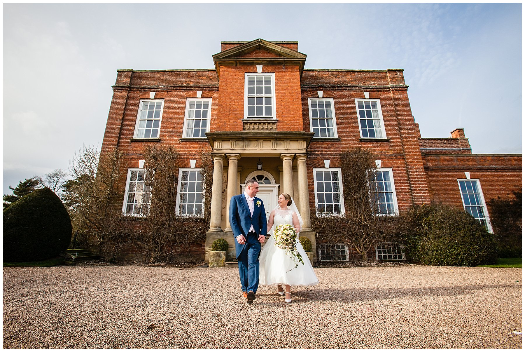 bride and groom looking at one another lovingly as iscoyd park is in the background - shropshire wedding photographer