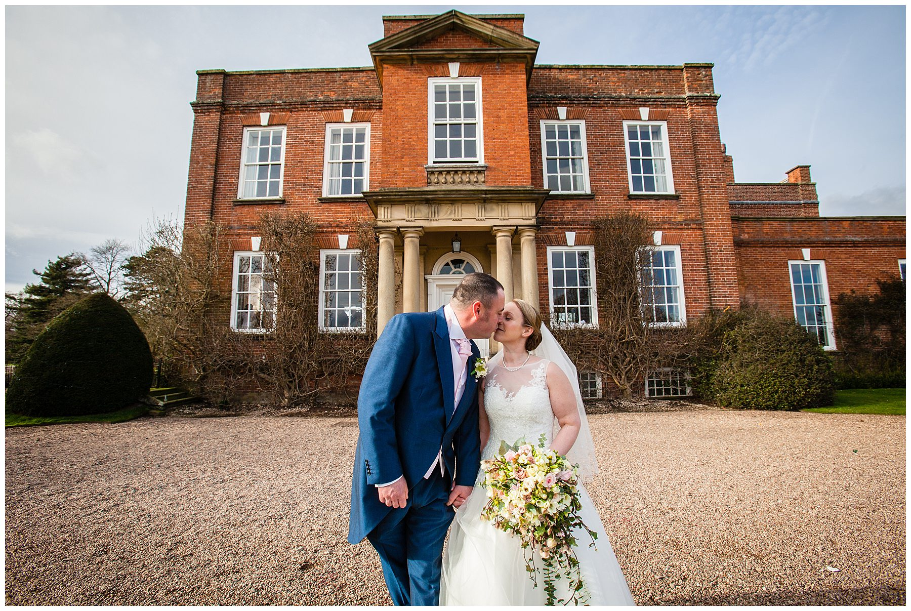 bride and groom having a kiss outside iscoyd park wedding venue - charlotte giddings photography