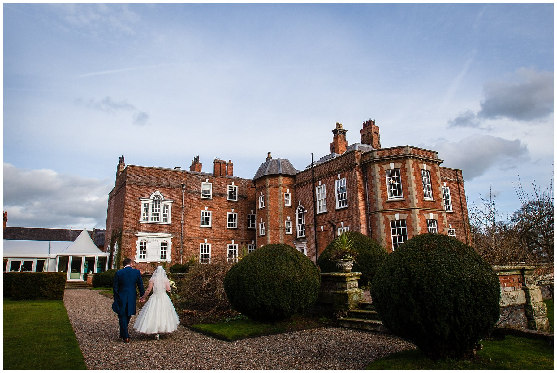 bride and groom walking back to the wedding reception in iscoyd park - charlotte giddings photography