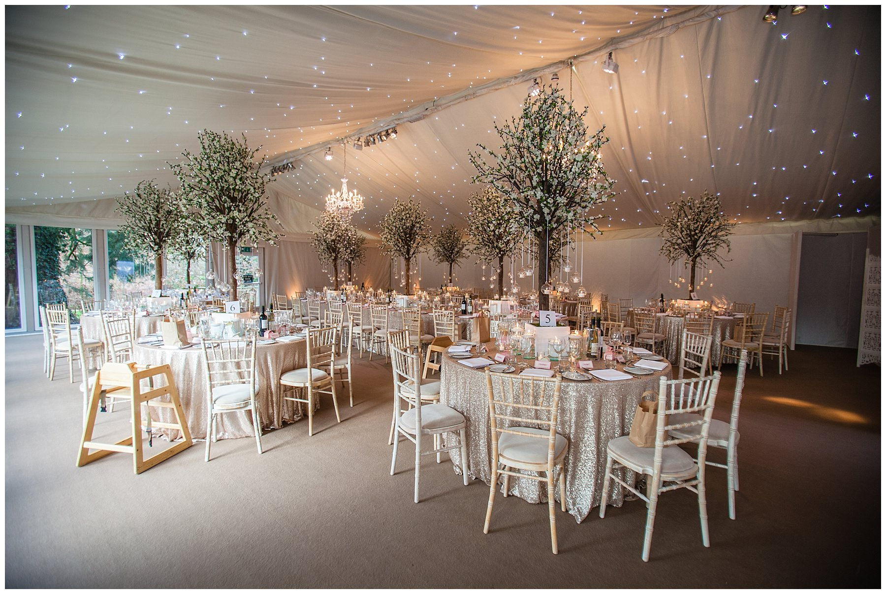 wide shot of the wedding breakfast room beautifully decorated with sequin table cloths and talk blossom trees and candles - iscoyd park
