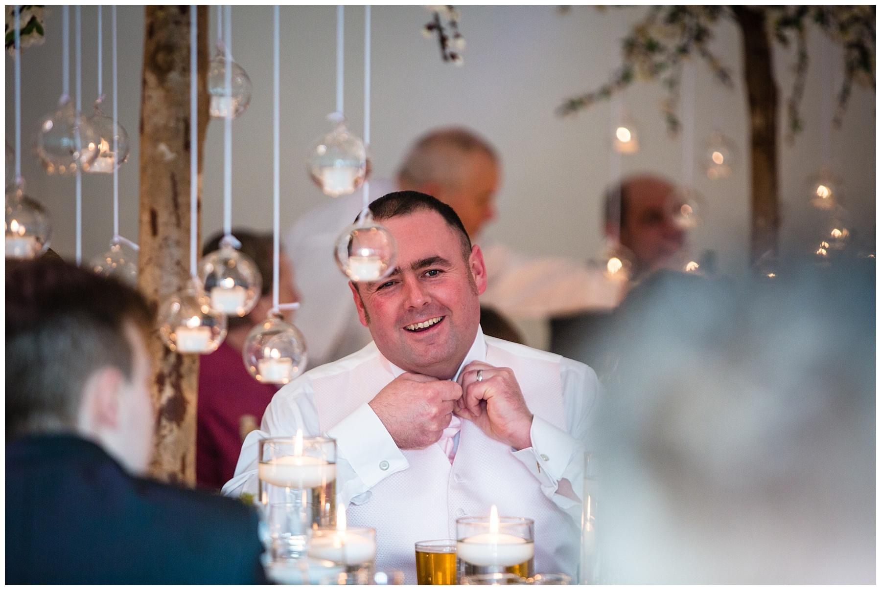 groom undoing top button on his shirt before the speeches begin - iscoyd park wedding photographer