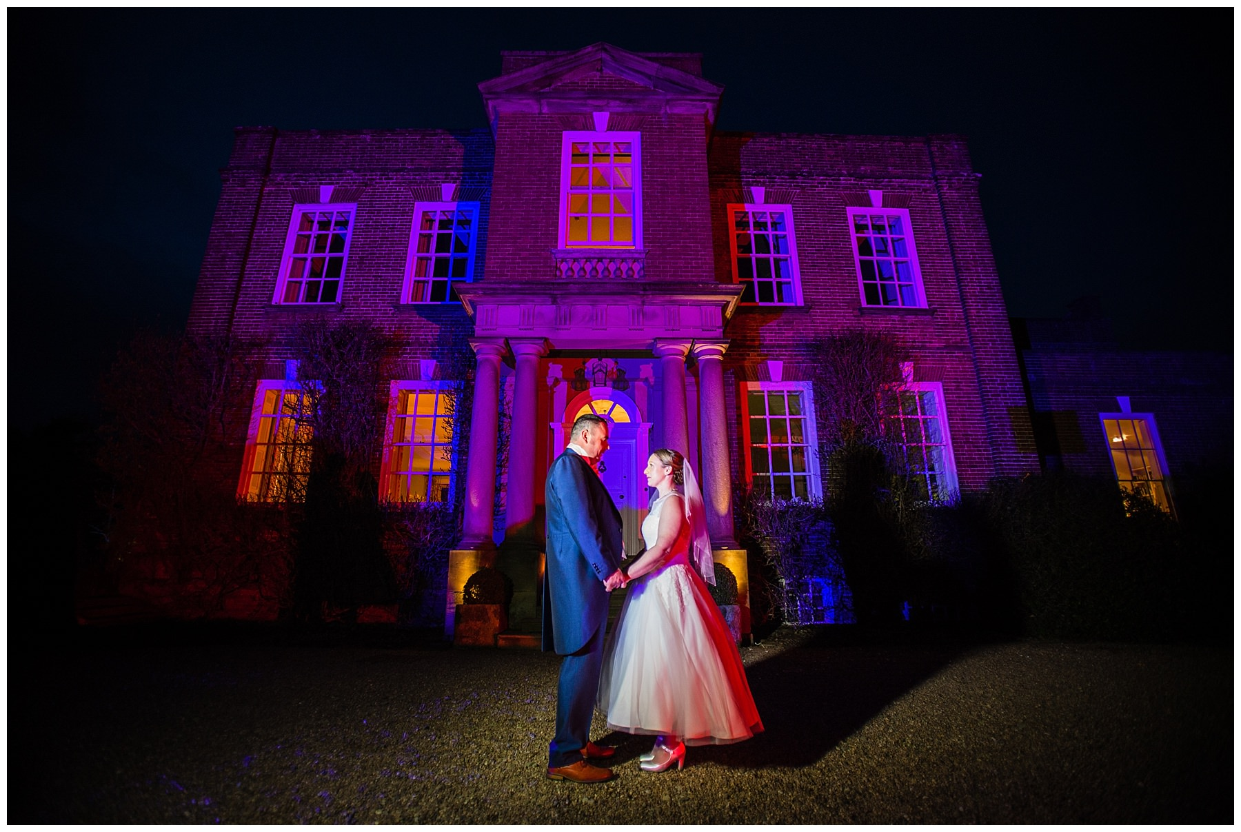 bride and groom portrait in front of iscoyd park in the dark and illuminated pink lights - charlotte giddings photography