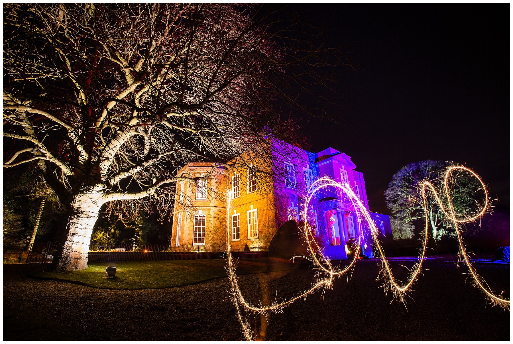 sparklers spelling love in front of iscoyd park wedding venue last at night in the dark - charlotte giddings photography