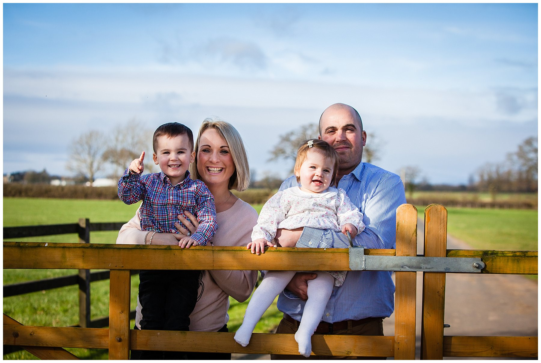 very happy family of four by farm gate all looking content - shropshire photographer
