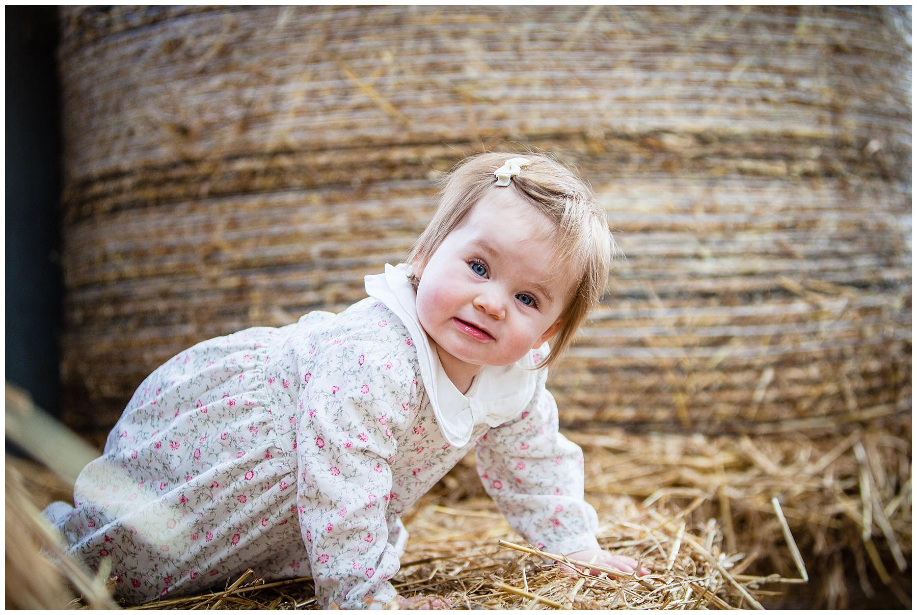 baby girl playing hide and seek inbetween the hay bales at cheshire family farm - shropshire portrait photographer