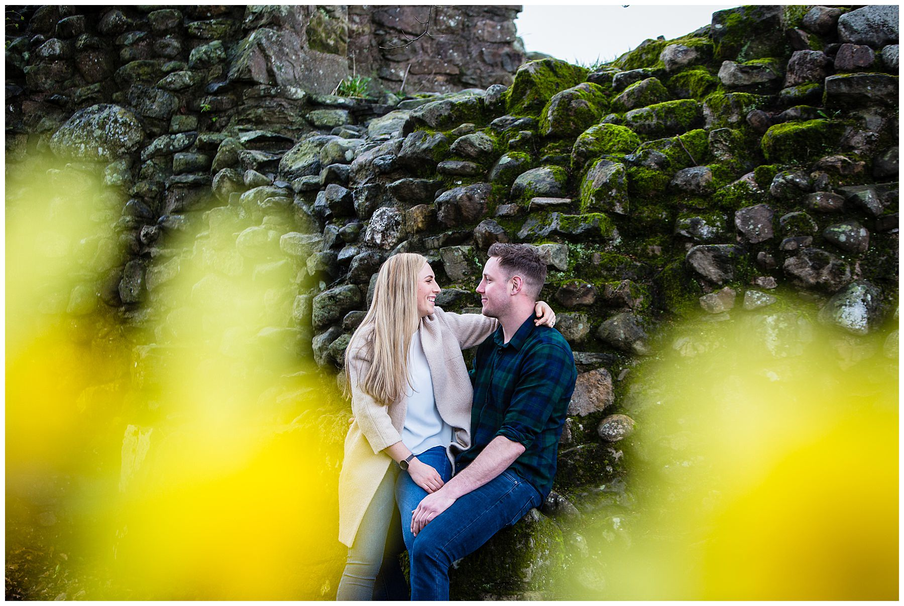 happy couple looking at one another with daffodils in the foreground - charlotte giddings photography