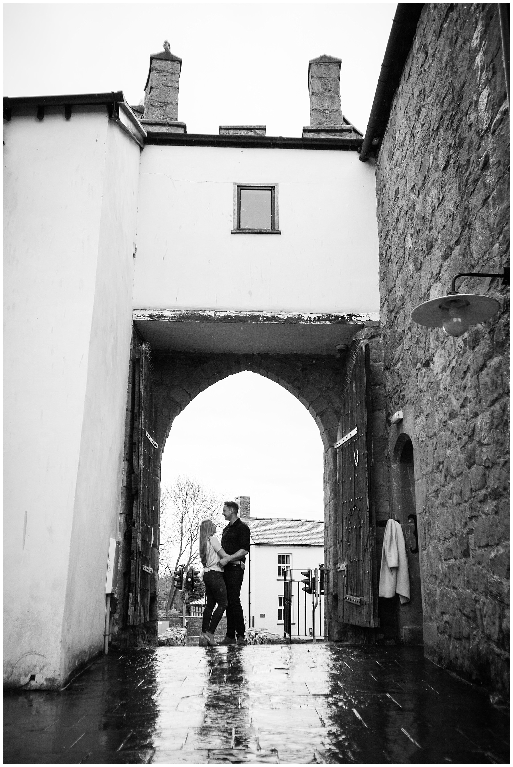 silhoutte on couple arm in arm in main doors at whittington castle - shropshire engagement shoot