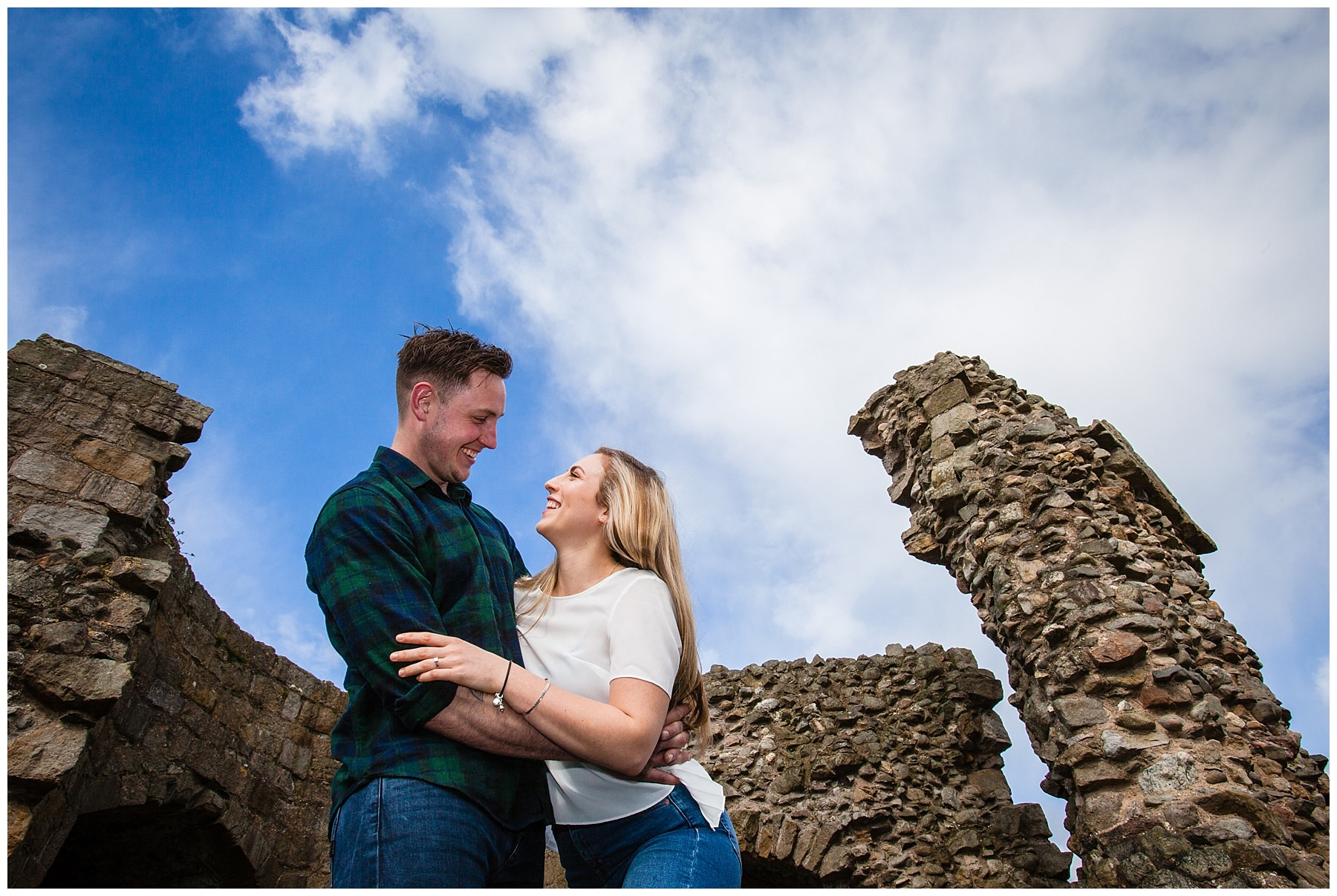 couple looking at each other with castle ruins and blue shy - shropshire engagement shoot