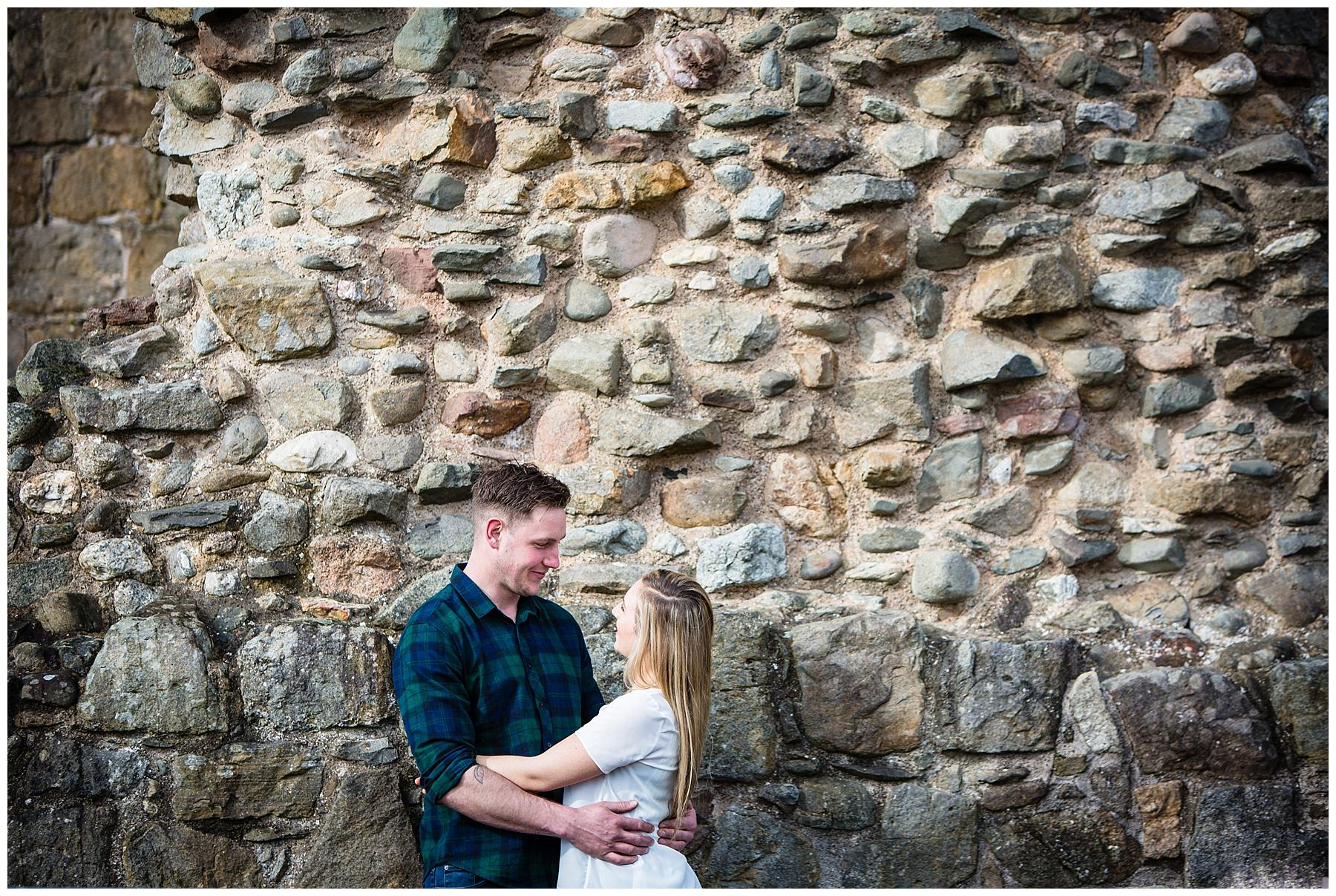 couple against castle ruins ackground, arms around one another - wedding photographer shropshire